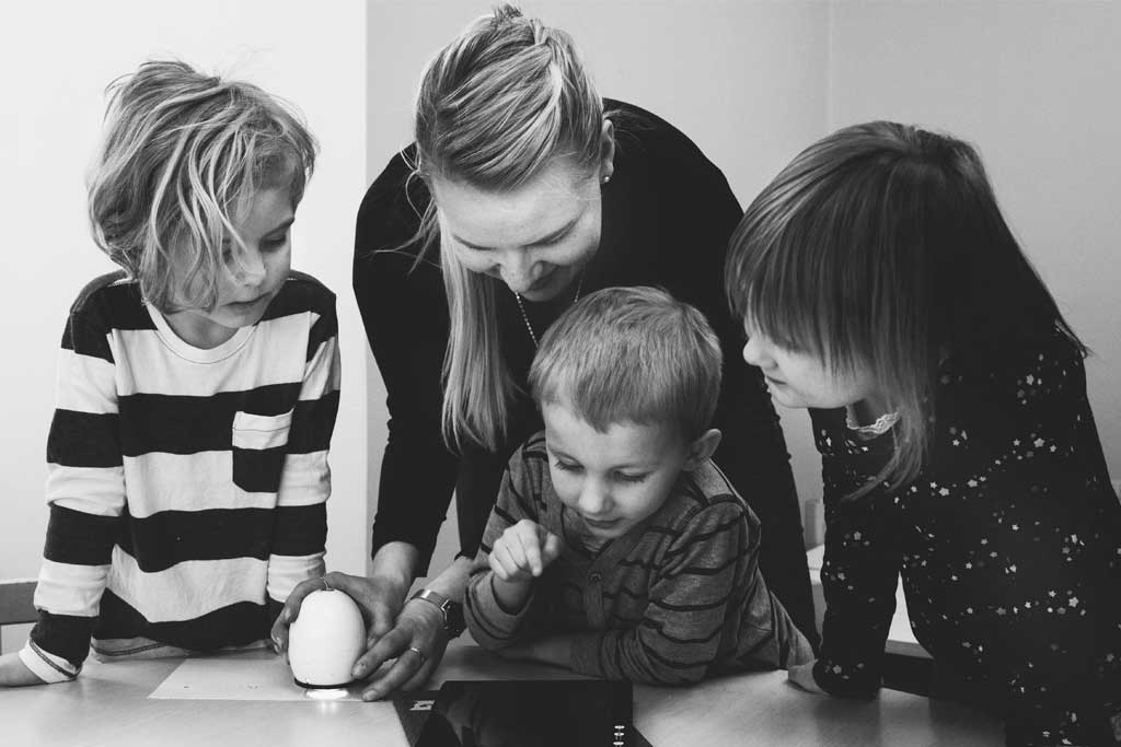 Black and white image of a mother and three children learning together.